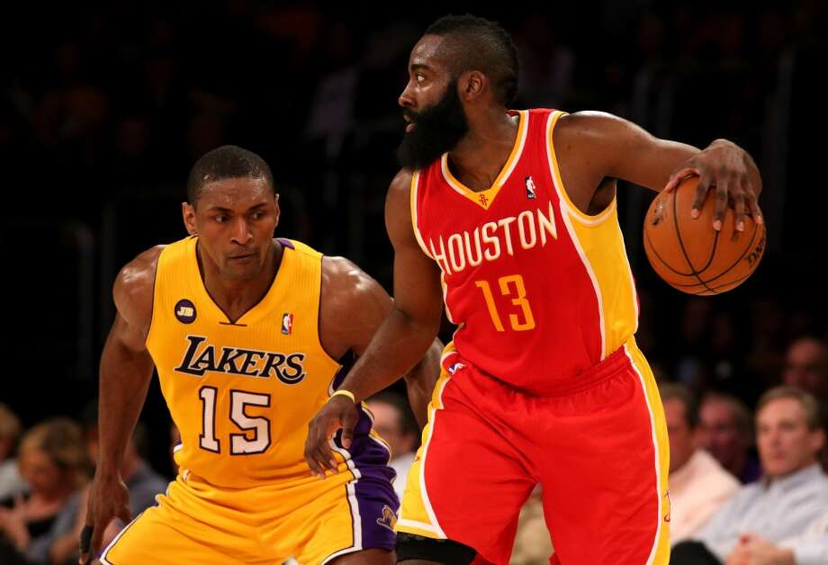 Rockets shooting guard James Harden dribbles while Lakers forward Metta World Peace defends.