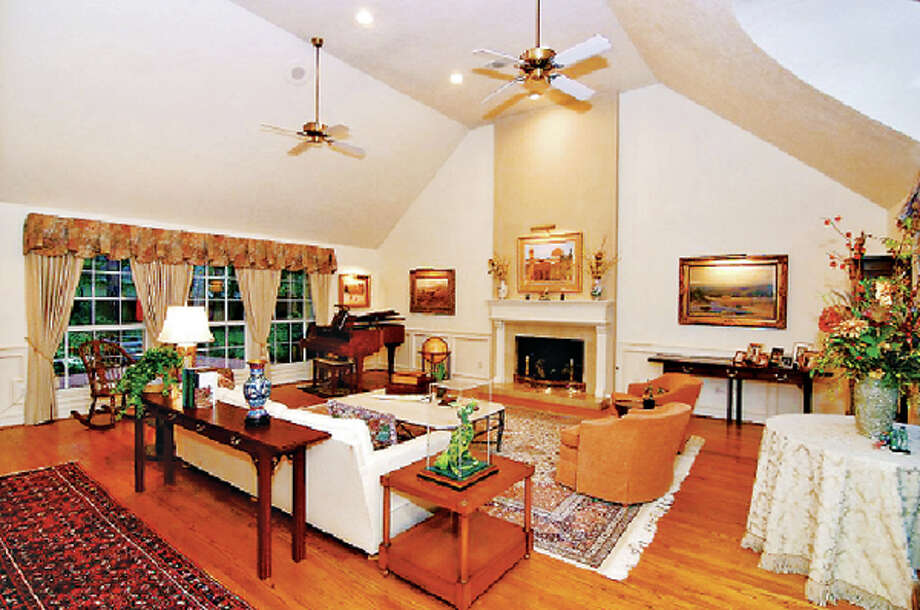 The living room features high ceilings, hardwood floors and a fireplace.
