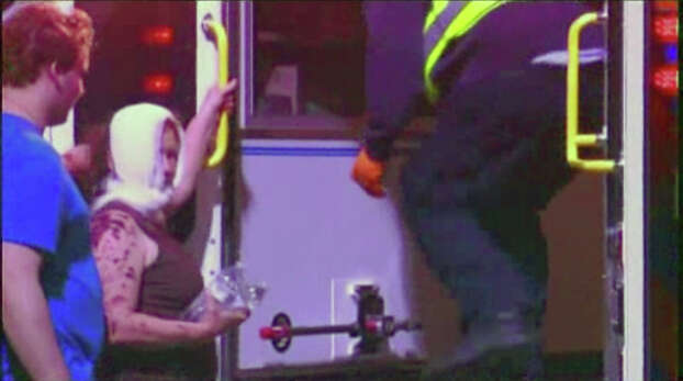 This video image porvided by KWTX-TV shows an injured woman from an explosion at a fertilizer plant near Waco Wednesday night April 17, 2013 being helped into a waiting ambulance in West Texas. The blast injured dozens of people and sent flames shooting high into the night sky, leaving the factory a smoldering ruin and causing major damage to surrounding buildings. (AP Photo/KWTX-TV) Photo: Associated Press / KWTX-TV
