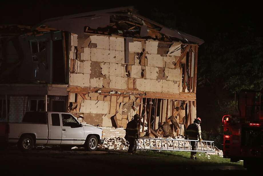 Rescue workers pass a damaged apartment complex after a nearby fertilizer plant exploded Wednesday, April 17, 2013, in West, Texas. (AP Photo/ Waco Tribune Herald, Rod Aydelotte) Photo: Rod Aydelotte, Associated Press