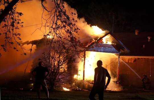 A person looks on as emergency workers fight a house fire after a near by fertilizer plant exploded Wednesday, April 17, 2013, in West, Texas. Photo:  Waco Tribune Herald, Rod Aydelotte