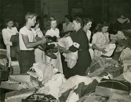 April 17, 1947: Some of the clothing and supplies received in large amounts by the Red Cross at the City Auditorium on Thursday afternoon are shown above. A Boy Scout volunteer worker, Kenneth Onarecker, is shown turning over some of the clothing he collected to Mrs. Lillian Crawford, chairman of clothing and supplies for the Red Cross at the Auditorium. Photo: Houston Chronicle Files / Houston Chronicle