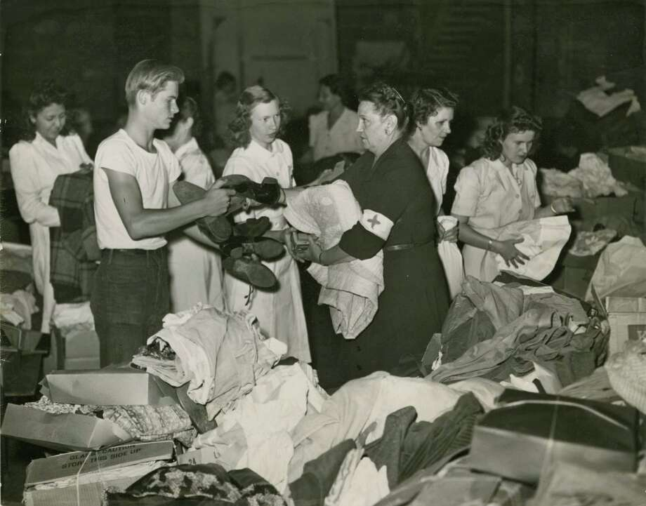 04/17/1947 - Texas City Disaster Red Cross relief collection at City Auditorium in Houston - Boy Scout Kenneth Onarecker passes donated clothes and shoes to Lillian Crawford, Red Cross worker serving as chairman of clothing and supplies.  Photo: Houston Chronicle Files / Houston Chronicle
