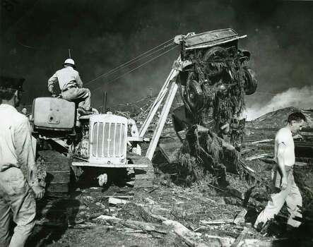 April 16, 1947: A portable crane raises a wrecked car from the wreckage caused by the explosion and fire. The search for dead and injured in the blast continues. Photo: Houston Chronicle / Houston Chronicle