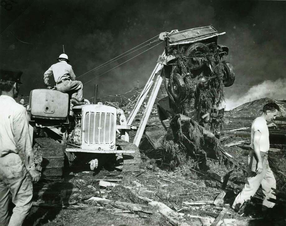 04/16/1947 - A portable crane raises a wrecked car from the wreckage caused by the explosion and fire. The search for dead and injured in the blast continues. Photo: Houston Chronicle / Houston Chronicle