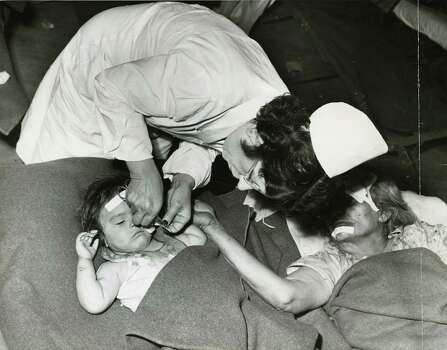 April 16, 1947: Apparently trying to help the nurse give first aid to an injured child is an older victim of the blast at one of the emergency aid stations set up in the city. Photo: Chester Rogers, Houston Chronicle / Houston Chronicle