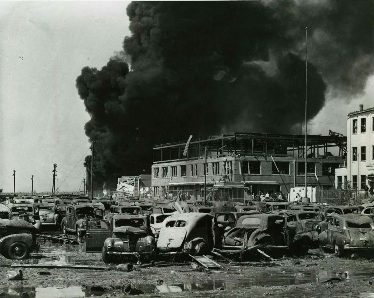 04/16/1947 - Crumpled and tossed about by the explosion were these cars in the parking lot of the Monsanto Chemical Corporation. Behind the cars may be seen the main office building of the company framed against a curtain of black smoke.