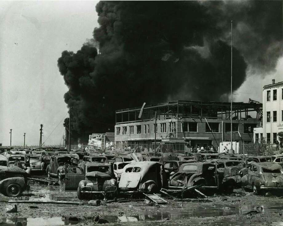 04/16/1947 - Crumpled and tossed about by the explosion were these cars in the parking lot of the Monsanto Chemical Corporation. Behind the cars may be seen the main office building of the company framed against a curtain of black smoke. Photo: Chester Rogers, Houston Chronicle / Houston Chronicle