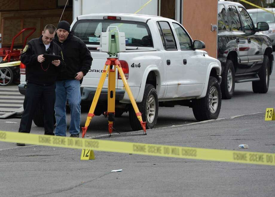 Albany Police forensics investigators use a satellite GPS tracking device to plot the scene of a fatal overnight shooting at King Street and Central Avenue Thursday morning, April 18, 2013, in Albany, N.Y.  (Skip Dickstein/Times Union) Photo: SKIP DICKSTEIN