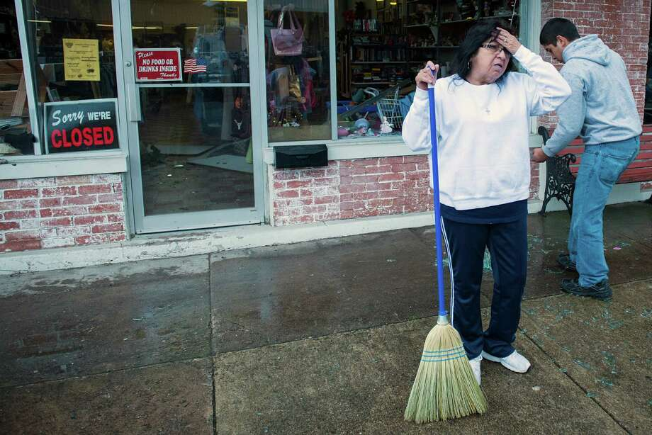 Maria Galvan pauses while sweeping up broken glass from the blown out front windows of the West Thirft Shop  on Thursday morning, April 18, 2013, in West, Texas. Photo: Smiley N. Pool, Houston Chronicle / © 2013  Houston Chronicle