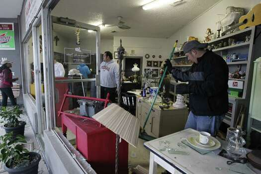 Bobby Rios, right, helps clean up the shattered display windows at Treasure on the Tracks in the central business district of West, Texas on Thursday April 18, 2013. A massive explosion at the West Fertilizer Co. killed as many as 15 people and injured more than 160, officials said overnight.  The explosion that struck around 8 p.m. Wednesday, sent flames shooting into the night sky and rained burning embers and debris down on shocked and frightened residents. (AP Photo/The Fort Worth Star-Telegram, Ron T. Ennis)  MAGS OUT; (FORT WORTH WEEKLY, 360 WEST); INTERNET OUT Photo: Ron T. Ennis, AP / The Fort Worth Star-Telegram