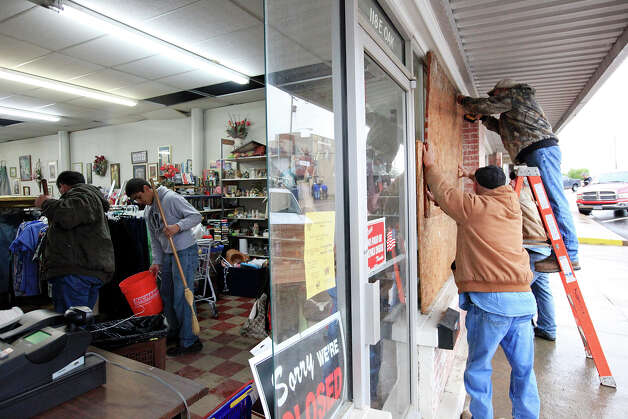 Workers sweep up glass and board up windows, Thursday April 18, 2013, at West Thrift Shop after an explosion at a fertilizer plant Wednesday evening in West, Tx. Photo: Edward A. Ornelas, San Antonio Express-News / © 2013 San Antonio Express-News