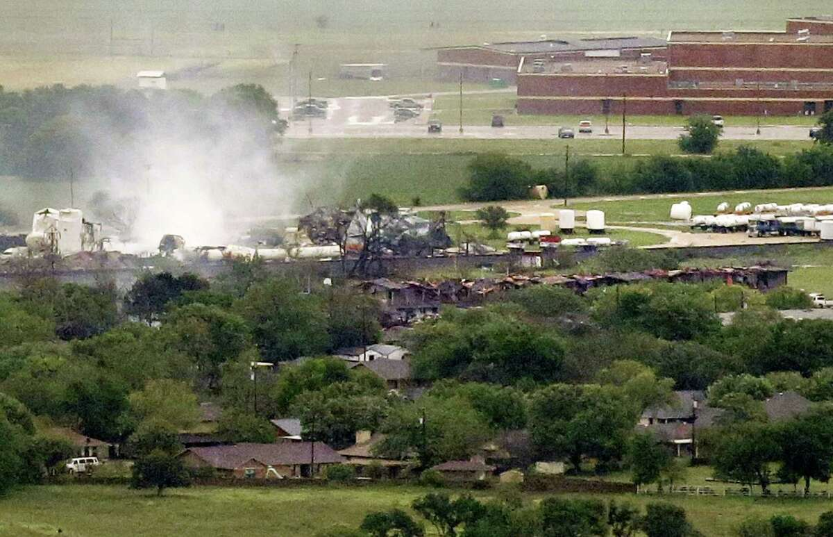 This aerial photo shows a local school, at rear, and an apartment complex, at middle right, near a fertilizer plant explosion site Thursday, April 18, 2013, in Near West, Texas. A massive explosion at the West Fertilizer Co. killed as many as 15 people and injured more than 160, officials said overnight. The explosion that struck around 8 p.m. Wednesday, sent flames shooting into the night sky and rained burning embers and debris down on shocked and frightened residents. (AP Photo/Tony Gutierrez)