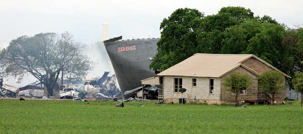 The smoldering remains, Thursday April 18, 2013, (left) of a fertilizer plant that exploded Wednesday evening in West, Tx. Photo: Edward A. Ornelas, San Antonio Express-News / © 2013 San Antonio Express-News