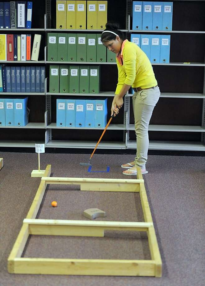 "Anything to keep them from reading: Reitz High School sophomore Courtney Adams putts on a makeshift miniature golf hole during National Library Week at the school's library. The course is just one of several ""interactive options"" for the Evansville, Ind., students to participate in during the week. Photo: Jason Clark, Associated Press"
