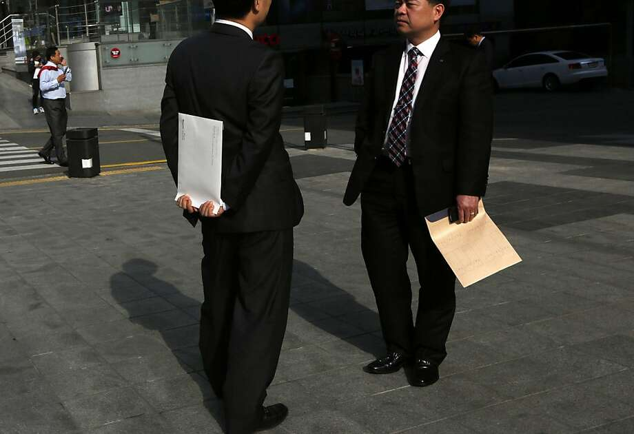 Of course I mailed it. Why do you ask? Two South Korean businessmen chat on a street in Seoul's Gangnam district. Photo: Kin Cheung, Associated Press