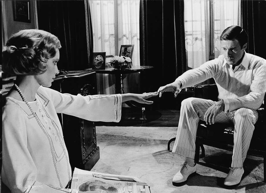 American actors Mia Farrow, as Daisy Buchanan, and Robert Redford, as Jay Gatsby, reach for one another across a room in a scene from 'The Great Gatsby,' based on the novel by F. Scott Fitzgerald and directed by Jack Clayton, 1974. Photo: Paramount Pictures, Getty Images / Moviepix