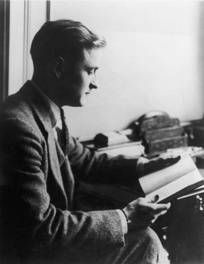 Profile view of American author F. Scott Fitzgerald reading a book while sitting at a desk. Photo: Hulton Archive, Getty Images / Archive Photos