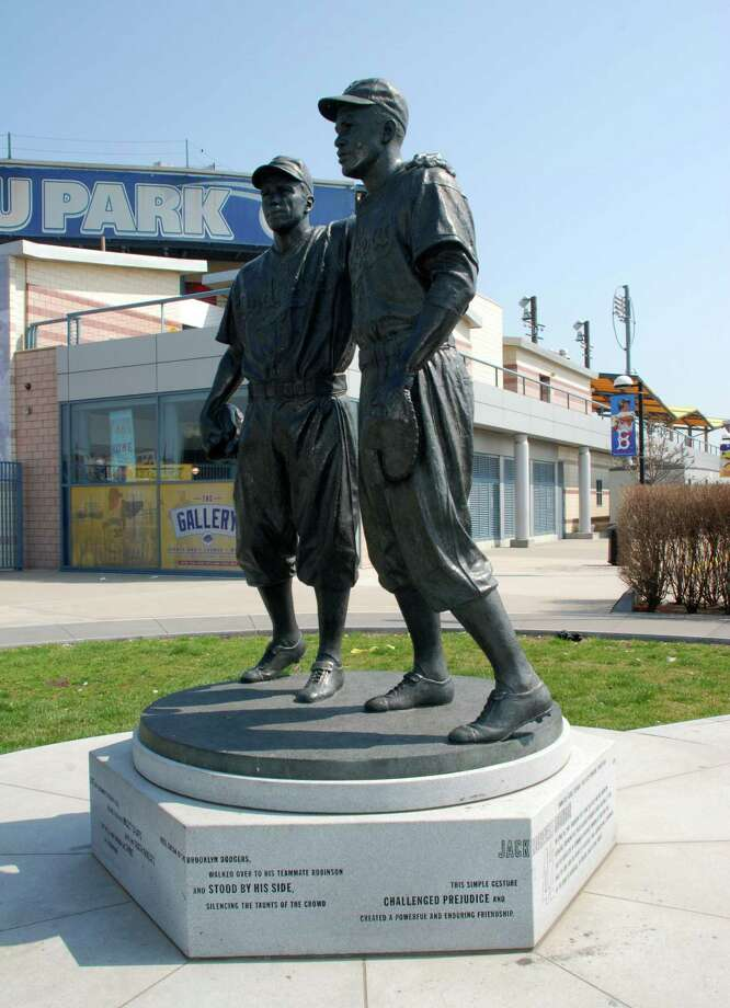A life-size statue on Coney Island portrays Jackie Robinson and Pee Wee Reese, the white Dodger who stood by him in the face of racist taunts. Photo: Brooklyn Cyclones / Associated Press