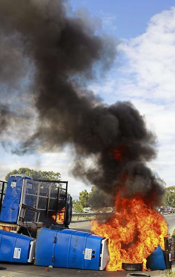 Smoking potties:A truck that carried temporary plastic toilets burns after townspeople set it afire near Khayelitsha township on the outskirts of Cape Town. The irate citizens had been demanding that brick toilet facilities be built in the township. Photo: Schalk Van Zuydam, Associated Press
