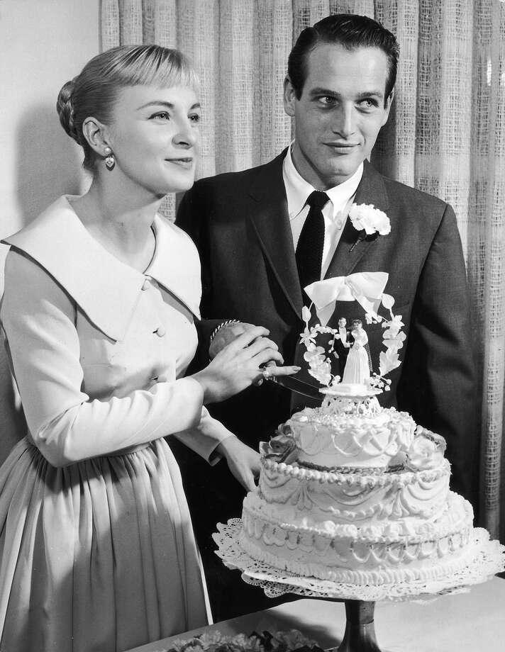 29th January 1958:  American actors Joanne Woodward, wearing a pale-colored dress with a pleated skirt, and Paul Newman, wearing a suit and tie, holding a knife together as they prepare to cut into their wedding cake, Las Vegas, Nevada. Photo: Hulton Archive, Getty Images / Archive Photos