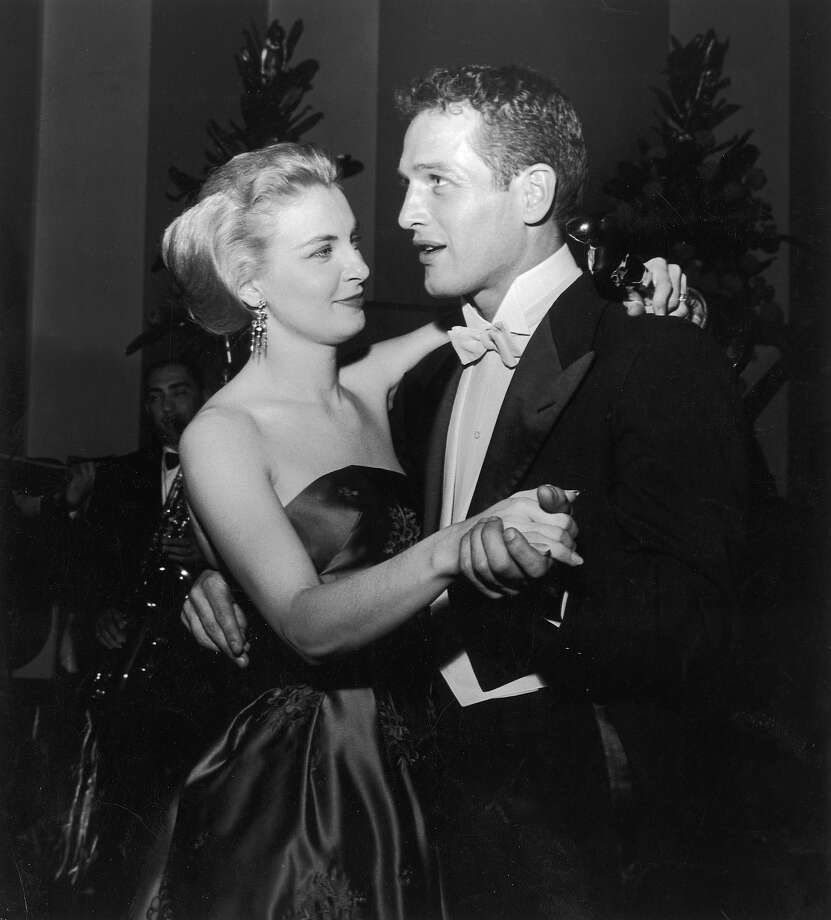 Married American actors Paul Newman and Joanne Woodward share a dance as Woodward holds her Best Actress Oscar statuette, during the Academy Awards party at the Beverly Hilton, Beverly Hills, California, March 26, 1958 . Woodward won the award for her starring role in the film, 'The Three Faces Of Eve,' directed by Nunnally Johnson. Photo: Darlene Hammond, Getty Images / 2002 Getty Images