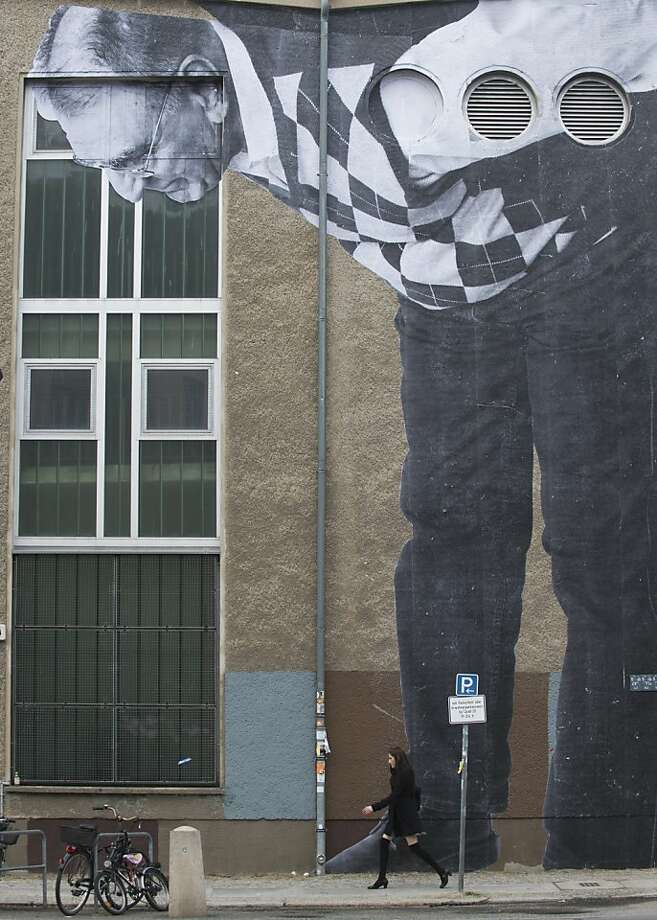 "Herr raising: A poster of an elderly man by French graffiti artist and self-coined ""photograffeur"" JR (he's known only by his initials) gazes down on a pedestrian in Berlin. The mural is part of his ""Wrinkles of the City"" project, which includes portraits of older individuals who have, over time, witnessed and experienced the upheaval and transformation of the city. Photo: John Macdougall, AFP/Getty Images"