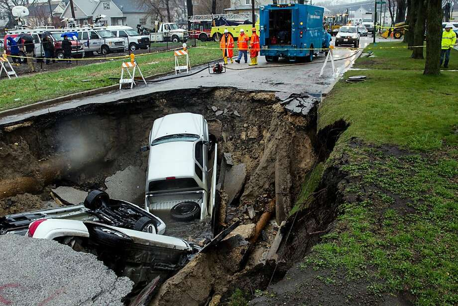 Pothole ahead: A sinkhole swallows three cars at 9600 South Houston Avenue in Chicago. One person was injured in the subsidence. Photo: Zbigniew Bzdak, McClatchy-Tribune News Service