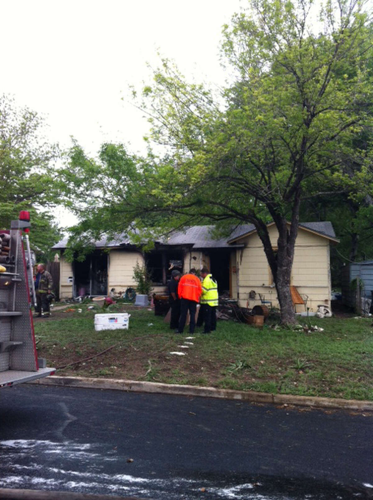 Firefighters examine the site of a house fire that left a woman in critical condition Thursday about 11 a.m. at the 100 block of Heather Avenue.