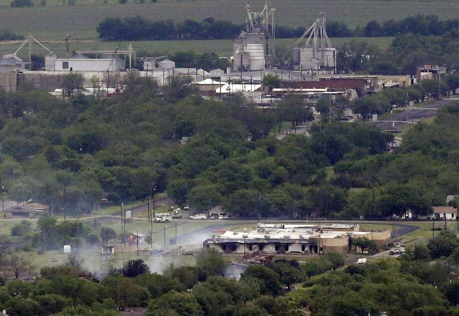 This aerial photo shows the remains of a fertilizer plant destroyed by an explosion in West, Texas, Thursday, April 18, 2013. A massive explosion at the West Fertilizer Co. killed as many as 15 people and injured more than 160, officials said overnight. The explosion that struck around 8 p.m. Wednesday, sent flames shooting into the night sky and rained burning embers and debris down on shocked and frightened residents. (AP Photo/Tony Gutierrez) Photo: Tony Gutierrez, Associated Press / AP