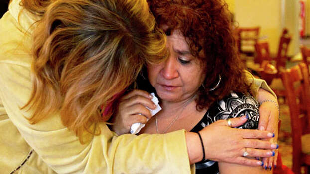 Janie Salazar, right, 57, of West weeps as she is held by her friend Iesha Chapman, 46, of Waco at the Best Western hotel. Salazar and her family had to evacuate her home. Photo: Johnny Hanson, . / © 2013  Houston Chronicle