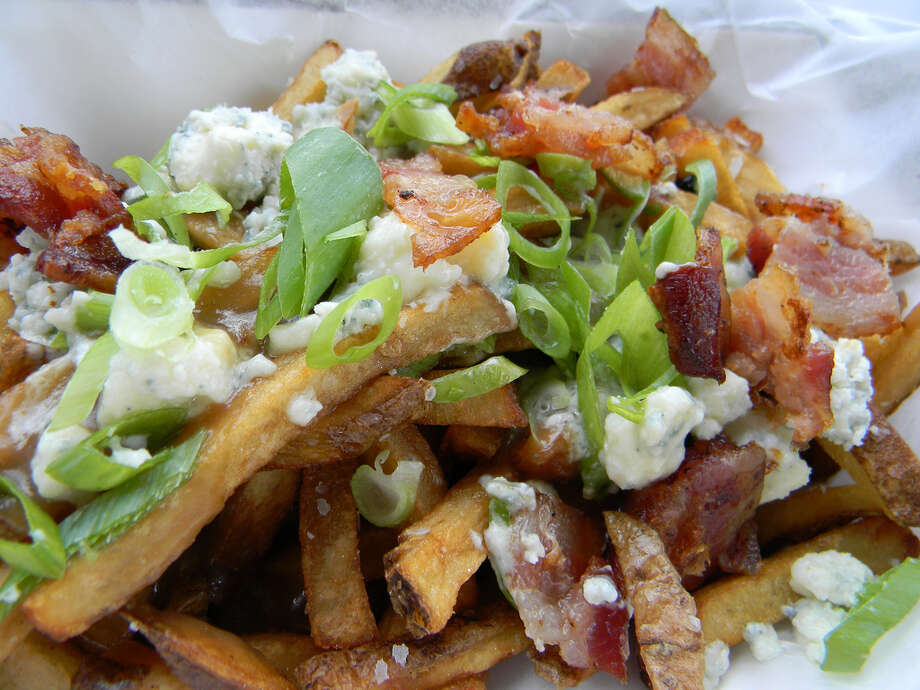 Poutine -- fries topped with gravy and cheese -- are a favorite snack food in Canada. The Wicked Whisk food truck in Houston adds bacon and green onion to the top of its version of poutine. Photo: Paul Galvani