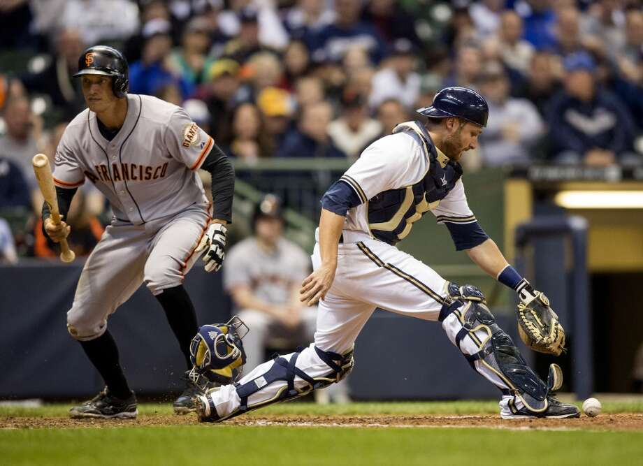 MILWAUKEE, WI - APRIL 18: Jonathan Lucroy #20 of the Milwaukee Brewers picks up the ball and prepares to throw to first as Hunter Pence #8 of the San Francisco Giants strikes out swinging in the eighth inning at Miller Park on April 18, 2013 in Milwaukee, Wisconsin.  (Photo by Tom Lynn/Getty Images)