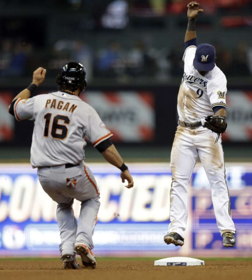 San Francisco Giants\' Angel Pagan (16) watches as Milwaukee Brewers\' Jean Segura (9) completes a double play on line drive hit by Gregor Blanco during the fifth inning of a baseball game Thursday, April 18, 2013, in Milwaukee.