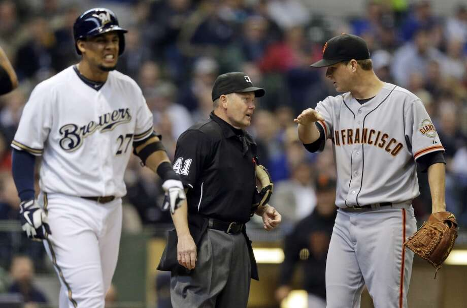 San Francisco Giants starting pitcher Matt Cain, right, argues with home plate umpire Kerwin Danley as Milwaukee Brewers\' Carlos Gomez (27) heads to first after being hit by a pitch during the second inning of a baseball game Thursday, April 18, 2013, in Milwaukee.