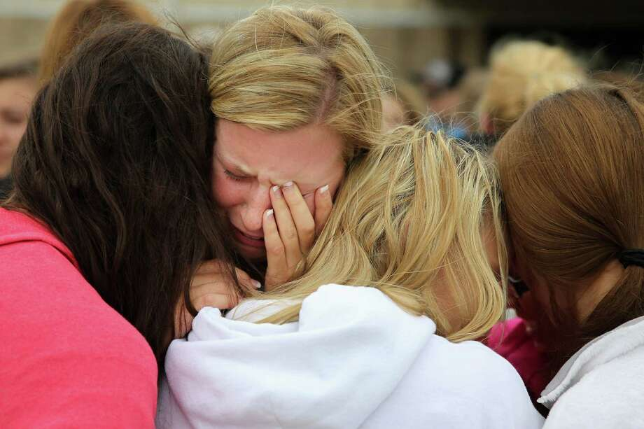 WEST, TX - APRIL 18:  West High School senior Mackenzie Wernet (C) is embraced by fellow students and friends after praying for the victims and survivors the day after the West Fertilizer Company explosion April 18, 2013 in West, Texas. Wernet's home was destroyed when the fertilizer company caught fire and exploded, injuring more than 160 people and leaving damaged buildings for blocks in every direction. Photo: Chip Somodevilla, Getty Images / 2013 Getty Images