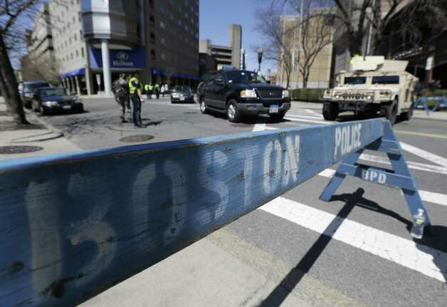 Officials stand guard near the site of the Boston Marathon explosions, Wednesday, April 17, 2013, in Boston. Authorities investigating the deadly bombings have recovered a piece of circuit board that they believe was part of one of the explosive devices, and also found the lid of a pressure cooker that apparently was catapulted onto the roof of a nearby building, an official said Wednesday. Photo: Julio Cortez
