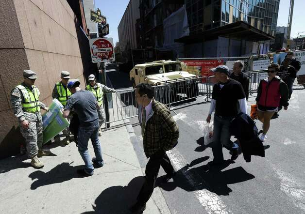 Military Police, left, inspect the identification card of a man trying to get through a checkpoint near the site of the Boston Marathon explosions, Wednesday, April 17, 2013, in Boston. The city continues to cope following Monday's explosions near the finish line of the marathon. Photo: Julio Cortez