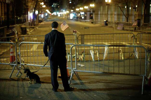 Marathon runner Benton Berman accompanied by his dog Tank pauses on Boylston Street near the finish line of Monday's Boston Marathon explosions, which killed at least three and injured more than 140, Wednesday, April 17, 2013, in Boston.  Berman said he was blocks away from finishing before the blasts occurred. Photo: Matt Rourke