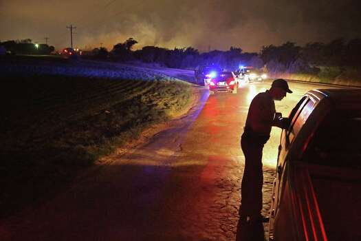 WEST, TX - APRIL 18:  With smoke rising in the distance, a law enformcement officer runs a check point at the perimeter about half a mile from the West Fertilizer Company April 18, 2013 in West, Texas. A massive explosion at the fertilizer company injured more than 100 people and left damaged buildings for blocks in every direction. The death toll from the blast, which occured as firefighters were tackling a blaze, is as yet unknown. (Photo by Chip Somodevilla/Getty Images)  *** BESTPIX *** Photo: Chip Somodevilla, Getty Images / 2013 Getty Images