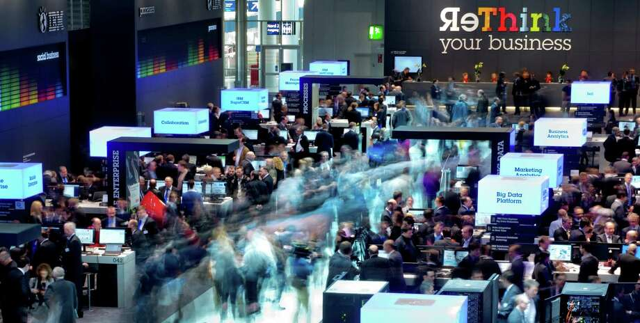 In this March 5, 2013, photo, made with a long exposure, visitors walk through the booths of IBM at the world's largest computer expo CeBIT in Hanover, Germany. Union Pacific Corp. reports quarterly financial results before the market opens Thursday, April 18, 2013. (AP Photo/dpa, Julian Stratenschulte) Photo: Julian Stratenschulte