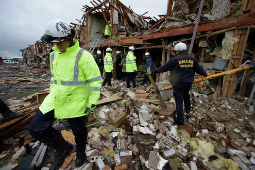 Firefighters conduct a search and rescue of an apartment building destroyed Wednesday by an explosion at a fertilizer plant in West, Texas, Thursday, April 18, 2013. The massive explosion at the plant killed as many as 15 people and injured more than 160, officials said overnight. (AP Photo/LM Otero) Photo: LM Otero, Associated Press / AP