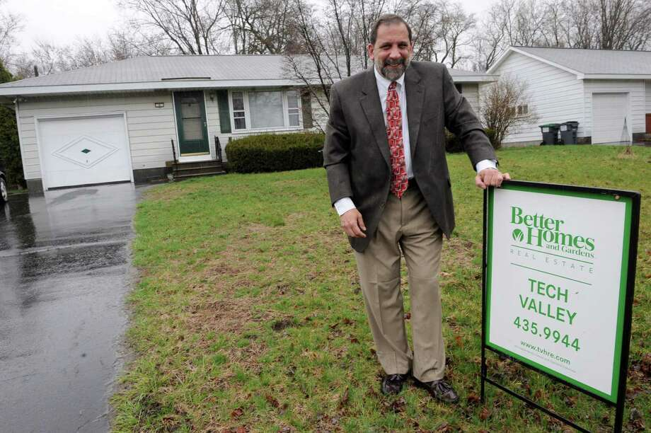 Miguel Berger, president of Greater Capital Association of Realtors, stands in front of a starter home for sale on Friday, April 12, 2013 in Colonie, N.Y.  (Lori Van Buren / Times Union) Photo: Lori Van Buren