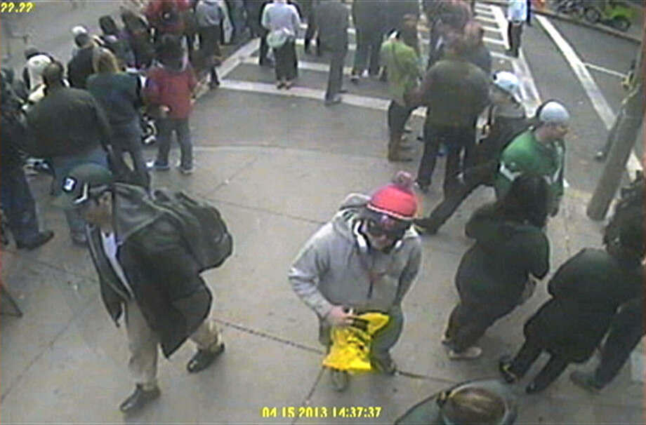 This image released by the FBI on Thursday, April 18, 2013, shows in a image from video what the FBI are calling suspect number 1, front left, in black cap, and suspect number 2, in white cap, back right, walking near each other through the crowd in Boston on Monday, April 15, 2013, before the explosions at the Boston Marathon. (AP Photo/FBI) Photo: FBI.gov
