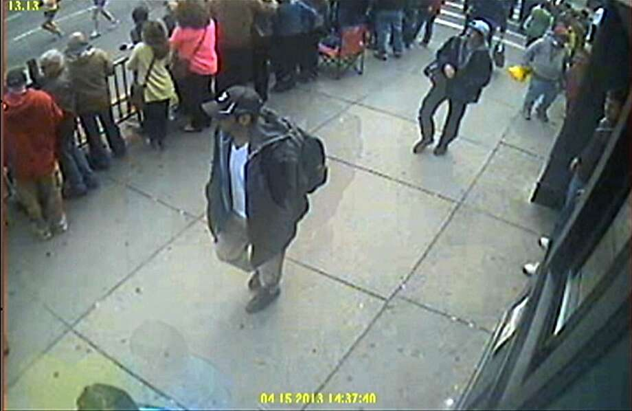 This image released by the FBI on Thursday, April 18, 2013, shows in a image from video what the FBI are calling suspect number 1, front, in black cap, and suspect number 2, in white cap, back right, walking near each other through the crowd in Boston on Monday, April 15, 2013, before the explosions at the Boston Marathon. (AP Photo/FBI) Photo: Associated Press