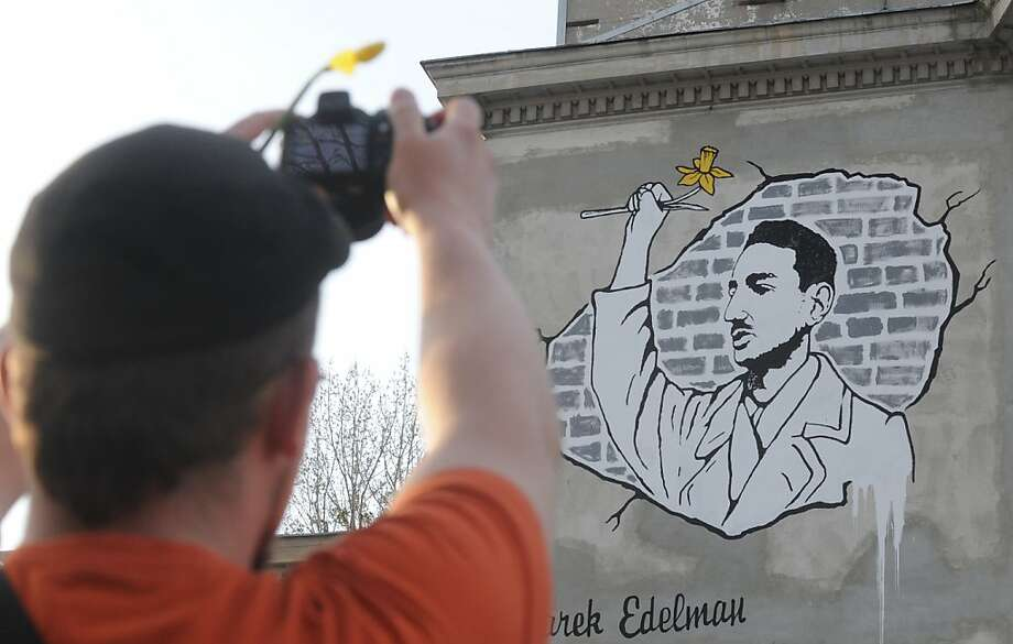 A man holding a daffodil takes a photo of a wall painting presenting Marek Edelman, the only Warsaw Ghetto 1943 Uprising commander who survived World War II, also holding a daffodil, on the eve of the 70th anniversary of the revolt,  in Warsaw, Poland, Thursday, April 18, 2013. Daffodils, which bloom in April, the month the uprising began, are a symbol of remembrance and hope, and were distributed to visitors viewing the graffiti. (AP Photo/Alik Keplicz) Photo: Alik Keplicz, Associated Press