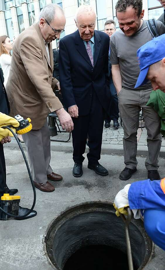 Simcha Rotem (center) peers into the sewer through which he and his comrades escaped the Nazis during the 1943 Warsaw ghetto uprising. Photo: Janek Skarzynski, AFP/Getty Images