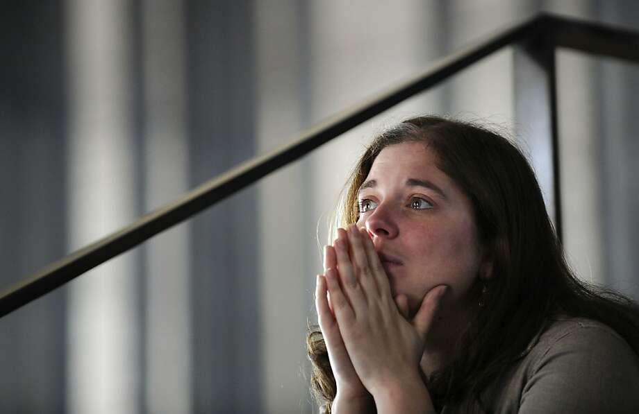 Afton Cotton listens to President Obama speak on television monitors in Boston. He talked about the victims during an interfaith healing service at Boston's Cathedral of the Holy Cross. Photo: Gretchen Ertl, New York Times