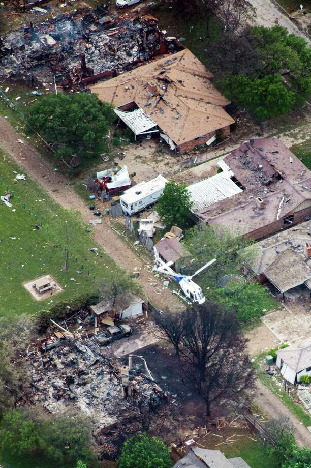 A law enforcement helicopter flies over homes damaged from the explosion of the West Fertilizer plant on Thursday, April 18, 2013, in West, Texas.  Photo: Smiley N. Pool, Houston Chronicle / © 2013  Houston Chronicle