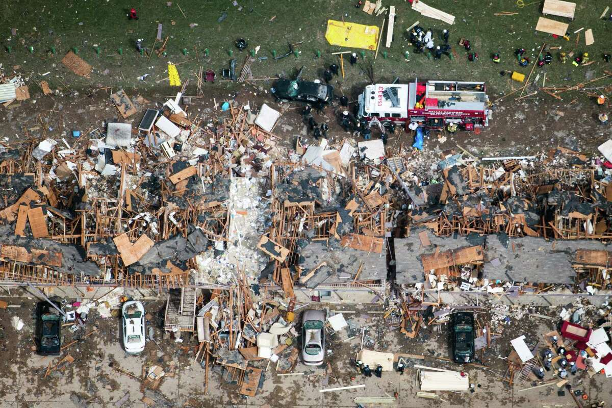 Law enforcement and rescue personnel search the damage to an apartment complex from the explosion of the West Fertilizer plant on Thursday, April 18, 2013, in West, Texas.